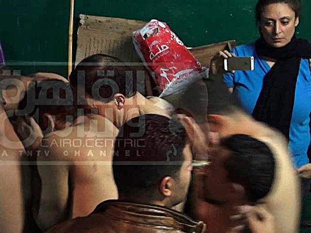 An image from Egyptian satellite channel Al-Qahira wa al-Nas shows journalist Mona Iraqi, (rear, right) photographing men arrested during a police raid on a public bathhouse in Cairo
