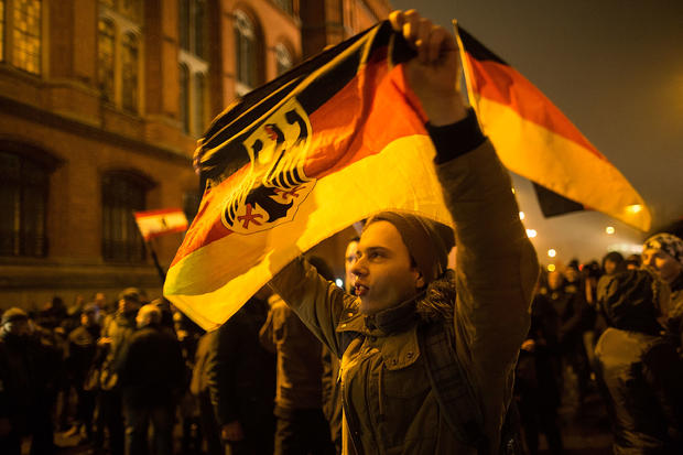 """A supporter of the PEGIDA movement holds a flag while supporters gather for a march in their first Berlin demonstration, which they have dubbed """"Baergida,"""""""