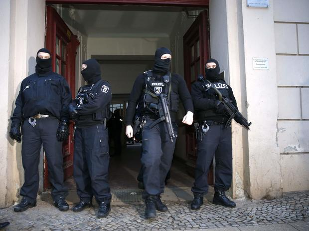 German special police units stand in front of an entrance of an apartment building in the Wedding district in Berlin