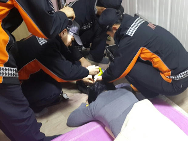 Firefighters try to remove a South Korean woman's hair from a robotic vacuum cleaner at her home
