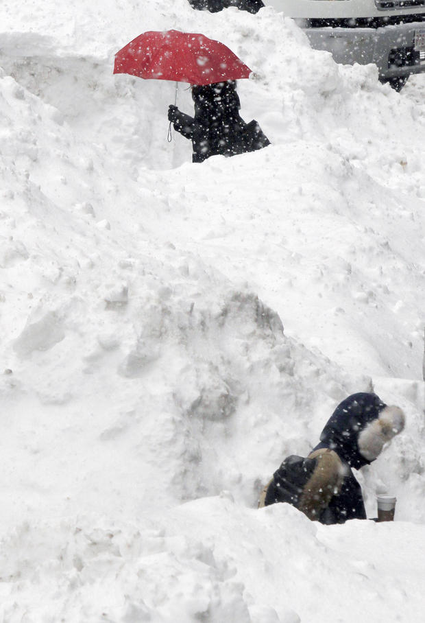 Commuters walk between piles of snow on a street in downtown Boston Feb. 11, 2015.