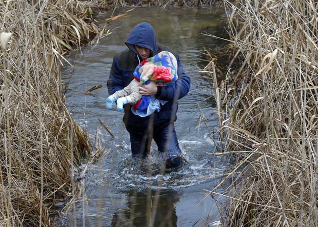 A man from Kosovo carries his baby as he illegally crosses the Hungarian-Serbian border near the village of Asotthalom, Hungary, Feb. 6, 2015.