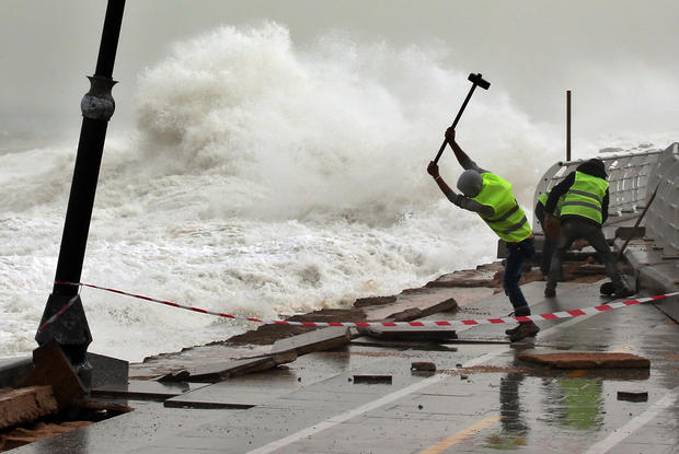 Municipal workers remove broken tiles near the fence of Beirut's seaside road, which was damaged by strong and high waves in Lebanon, Feb. 11, 2015.