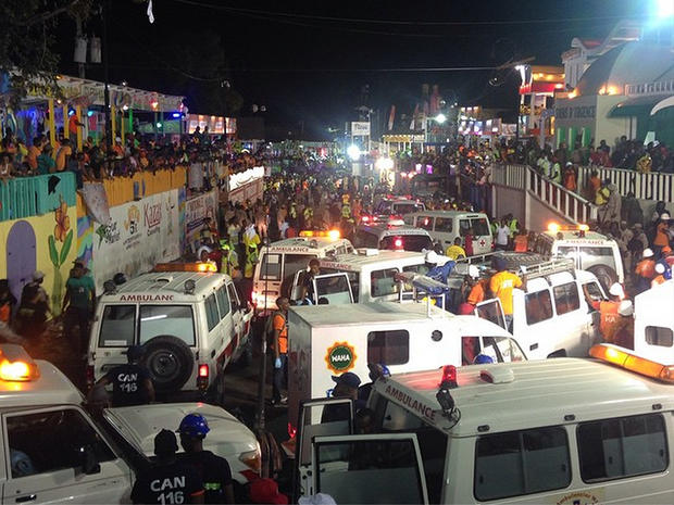Emergency service vehicles and personnel attend the scene of a fatal accident during a Carnival float procession in Port-au-Prince