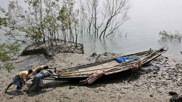 Villagers help a couple push their fishing boat to the water at Satyanarayanpur village in the Sundarbans