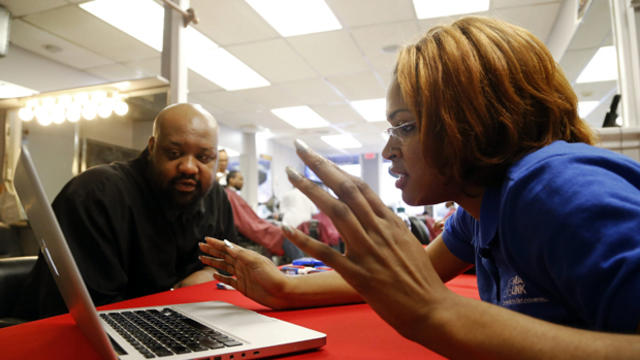 Karima Williams of DC Health Link assists barber Cornel Henry with health insurance information during an event for National African American Enrollment Week of Action, an initiative of the White House and U.S. Department of Health and Human Services, at
