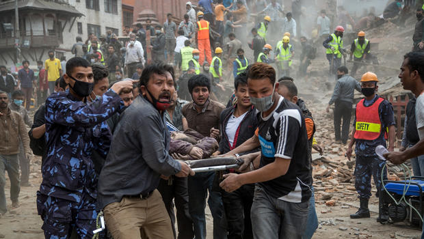 Emergency rescue workers carry a victim on a stretcher after Dharahara Tower collapsed from an earthquake April 25, 2015, in Kathmandu, Nepal.