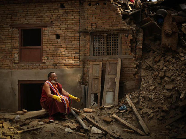 A Buddhist monk pauses during search efforts for earthquake victims in Sankhu, northeast of Kathmandu