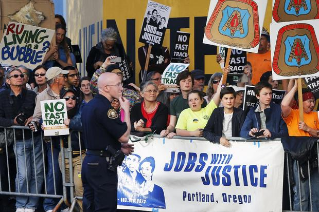 Protesters, many against the so-called fast track trade authority of the Trans-Pacific Partnership (TPP) trade agreement, rally outside the hotel where President Obama is participating in a Democratic National Committee (DNC) event