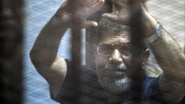 Egypt's deposed Islamist president Mohammed Morsi raises his hands from behind the defendant's cage as the judge reads out his verdict sentencing him and more than 100 other defendants to death at the police academy in Cairo May 16, 2015.