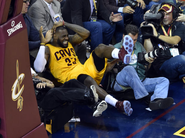 LeBron James falls into cameraman on sidelines during second quarter of Game 4 of NBA Finals at Quicken Loans Arena in Cleveland on June 11, 2015; Warriors won, 103-82