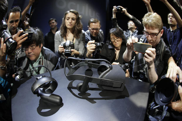 Photographers take pictures of the new Oculus Rift virtual reality headset and touch input device following a news conference June 11, 2015, in San Francisco.