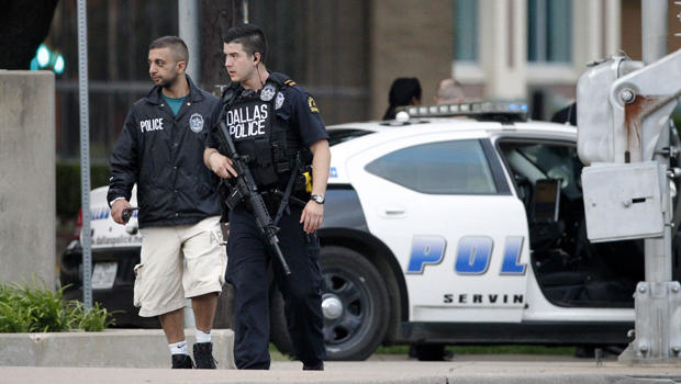 Dallas police officers walk down Belleview Street, one block away from police headquarters, searching the area June 13, 2015, in Dallas.