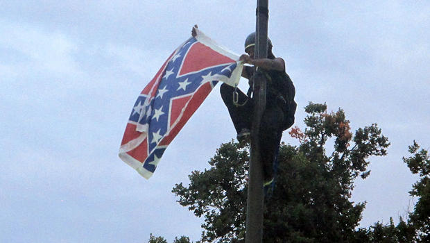 Bree Newsome of Charlotte, N.C., removes the Confederate battle flag at a Confederate monument at the Statehouse in Columbia, S.C., June 27, 2015.