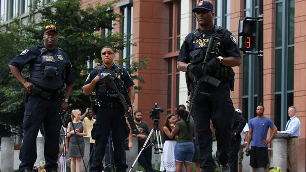 Law enforcement officials secure M Street in front of the Navy Yard facility where there was a report of shots fired July 2, 2015, in Washington.