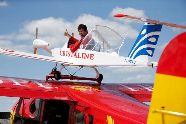 "Pilot Hugues Duval in his twin-engined ""Cri-Cri"", one of the world's smallest electrical planes, waits to take off from an old Broussard aircraft, on which it is attached to, during a flying display at the 51st Paris Air Show at Le Bourget airport near Paris"