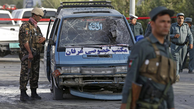 Afghan security personnel inspect a damaged vehicle at the site of a bomb blast in Kabul, Afghanistan, Aug. 22, 2015.