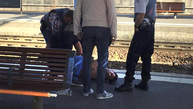 French police stand over a man who is apprehended on the platform at the Arras train station after shots were fired on the Amsterdam to Paris Thalys high-speed train in Arras, France, Aug. 21, 2015.