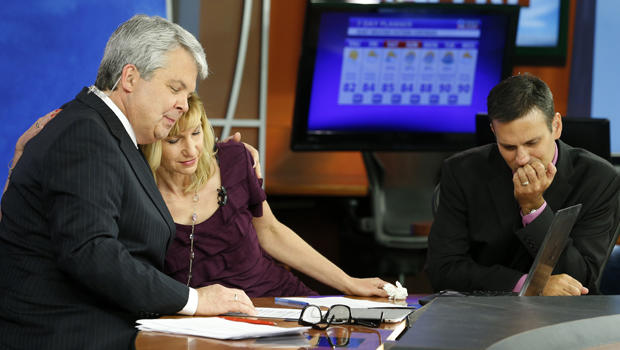 WDBJ-TV7 news morning anchor Kimberly McBroom, center, gets a hug from visiting anchor Steve Grant, left, as meteorologist Leo Hirsbrunner reflects after their early morning newscast at the station Aug. 27, 2015, in Roanoke, Va.