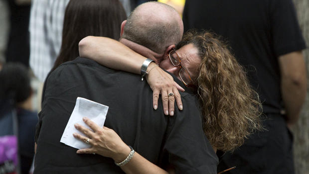 People embrace during a ceremony marking the 14th anniversary of the 9/11 attacks at the National September 11 Memorial and Museum in Lower Manhattan in New York Sept. 11, 2015.