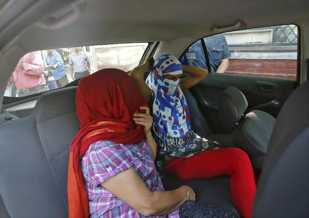 Two veiled Nepali women, who told police they were raped by a Saudi official, sit in a vehicle outside Nepal's embassy in New Delhi