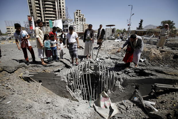 People gather at the site of a Saudi-led air strike which targeted a tunnel leading to the presidential house near the Petrol Station in Yemen's capital Sanaa