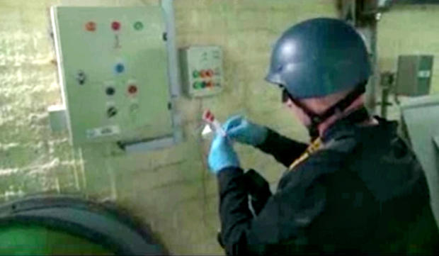 This file image made from video broadcast on Syrian State Television on Oct. 8, 2013, purports to show a chemical weapons expert taking samples at a chemical weapons plant at an unknown location in Syria.