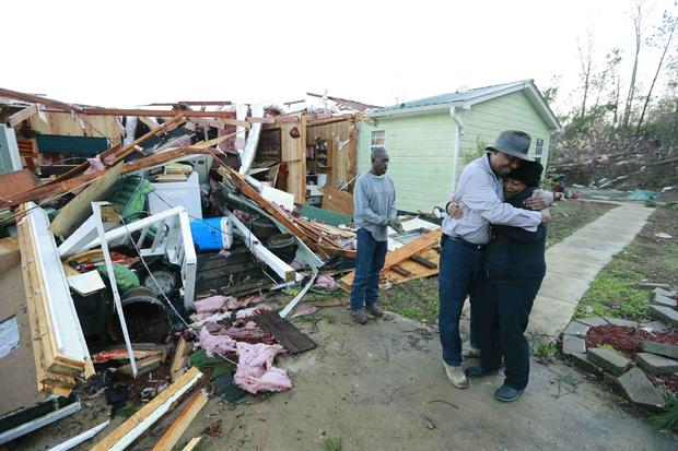 Phyllis Evans gets a hug from Harvey Payne early on December 24, 2015 after he stopped by to check on her and her home after a tornado struck Holly Springs, Mississippi
