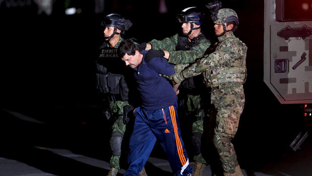 """Drug lord Joaquin """"El Chapo"""" Guzman is escorted by soldiers during a presentation in Mexico City Jan. 8, 2016."""
