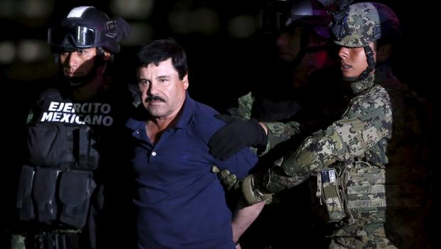 "Joaquin ""El Chapo"" Guzman is escorted by soldiers during a presentation at the hangar belonging to the office of the attorney general in Mexico City, Mexico, Jan. 8, 2016."