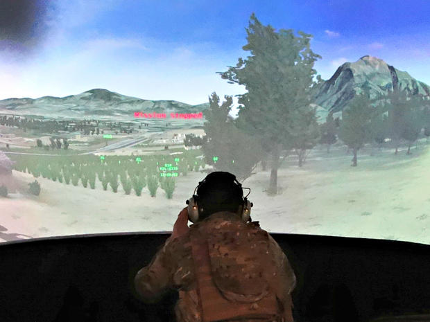 U.S. Air Force Staff Sgt. Bobby McDonald sits in front of a large screen depicting a simulated battle field, to practice calling in precision airstrikes during joint U.S.-Latvian military exercises at a base in Ādaži, Latvia