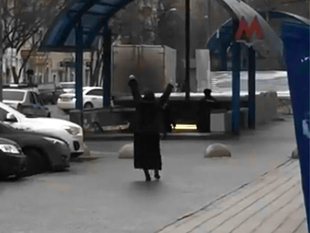 This screengrab from video posted to YouTube shows a woman who appears to be holding the severed head of a child while shouting at passersby outside the entrance to the Oktyabrskoye Pole metro station in northwest Moscow