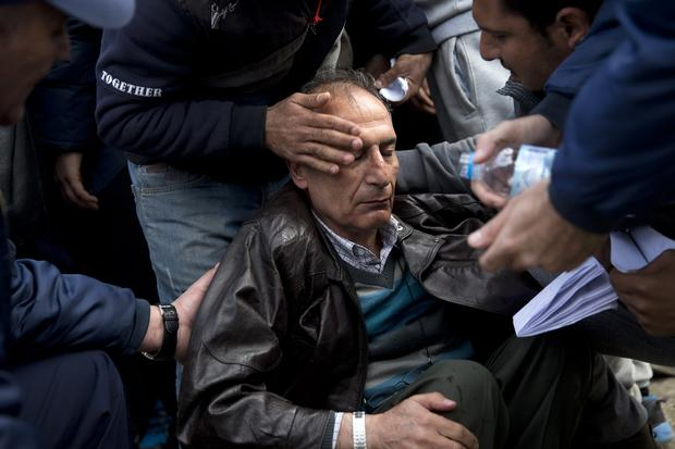 Greek police and migrants help a man who fainted after being turned back by Macedonian border authorities at the Idomeni crossing because of irregularities in his identity papers, near the northern Greek village of Idomeni