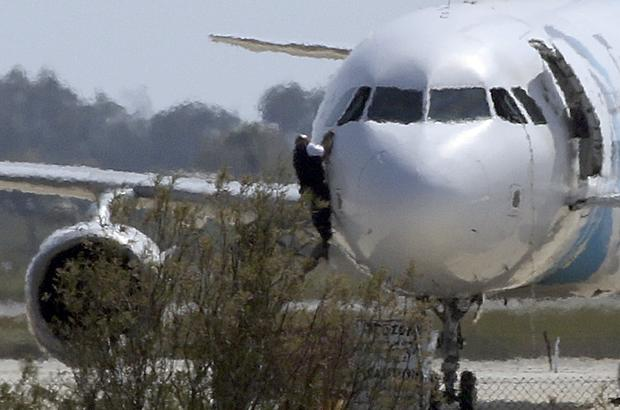A man climbs out of the cockpit window of the hijacked Egyptair Airbus A320 at Larnaca Airport in Larnaca
