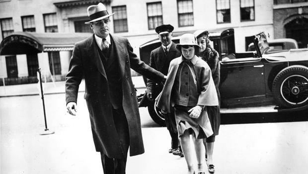 Accompanied by a bodyguard, a nurse, and a chauffeur, Gloria Vanderbilt enters the home of her mother, Gloria Morgan Vanderbilt, in Manhattan, April 22, 1935, for a Easter weekend visit.