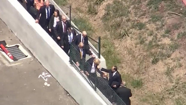 Donald Trump hops a wall to reach the Hyatt Regency hotel in Burlingame, California, on April 29, 2016.