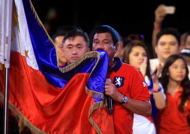 Philippine presidential candidate and Davao city mayor Rodrigo Duterte kisses the Philippine flag during a political campaign rally before the national elections at Rizal park in Manila, Philippines