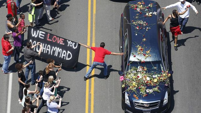 A well-wisher holding a banner touches the hearse carrying the remains of Muhammad Ali during the funeral procession for the three-time heavyweight boxing champion in Louisville, Kentucky, June 10, 2016.