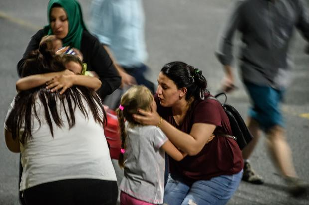 Relatives embrace as they leave Istanbul's Ataturk Airport after June 28, 2016 assault that took dozens of lives and wounded dozens more