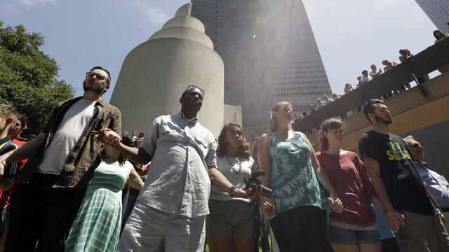 People take part in a prayer vigil at Thanksgiving Square, July 8, 2016, in Dallas.