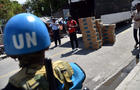 A United Nations Stabilization Mission in Haiti (MINUSTAH) soldier from Guatemala stands guard while Provisional Electoral Council members deliver electoral materials in Port-au-Prince on Oct. 24, 2015.