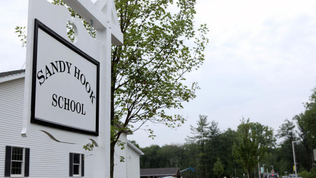 ​The sign for the new Sandy Hook Elementary School is pictured at the end of the drive leading to the school in Newtown, Connecticut, July 29, 2016.