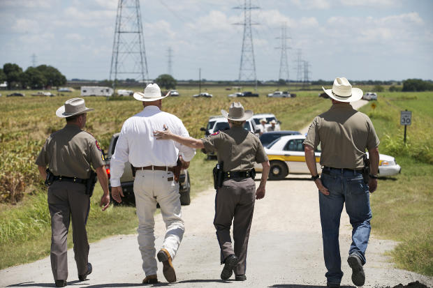 """Texas Department of Public Safety Trooper Robbie Barrera, center right, puts her arm around Caldwell County Sheriff Daniel Law as he arrives on the scene of a hot air balloon crash July 30, 2016, near Lockhart, Texas, causing what authorities described as a """"significant loss of life."""""""