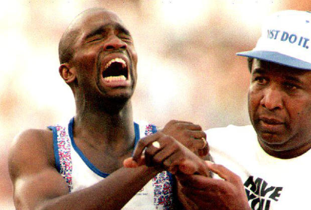 ​Derek Redmond, left, of Great Britain is helped by his father Aug. 3, 1992, in Barcelona, Spain, after suffering a torn hamstring during a second-round heat of the men's 400-meter run at the 1992 Summer Olympics.