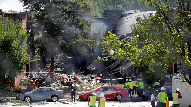 Firefighters look through the debris of a four-story building that was destroyed in a deadly explosion in Silver Spring, Maryland, Aug. 11, 2016.