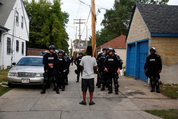 Police in riot gear assemble in an alley after disturbances following the police shooting of a man in Milwaukee, Wisconsin, Aug. 15, 2016.