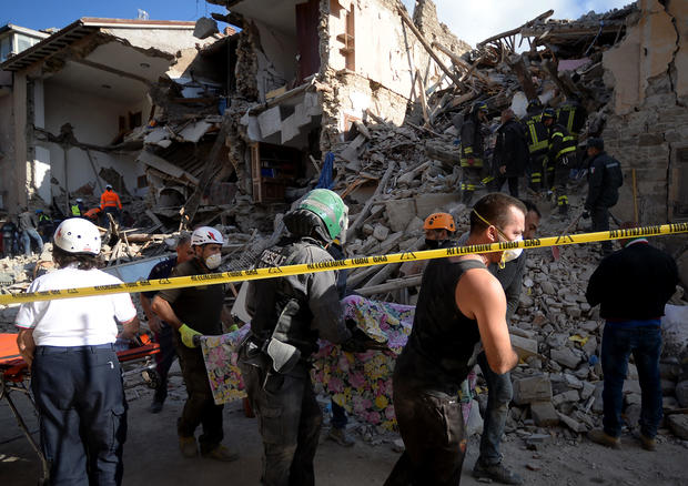 Rescuers carry the body of a victim next to the rubble of buildings in Amatrice
