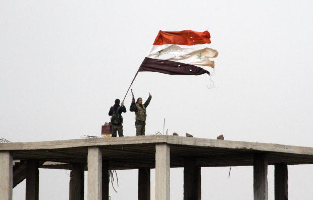 Syrian government forces wave the Syrian flag while standing on top of a building in Deir al-Adas, Syria, on Feb. 11, 2015, after President Bashar Assad's army, backed by Hezbollah and Iranian officers, pushed rebels out of the area.