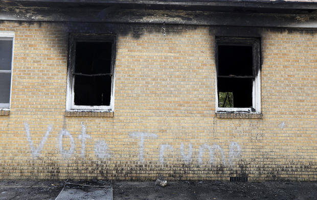"""Vote Trump"" is spray-painted on the side of the fire-damaged Hopewell M.B. Baptist Church in Greenville, Miss., Nov. 2, 2016."