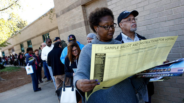 Mavis Wilson looks over a sample ballot as she waits to early vote with her husband, Ron Wilson, at Charlotte Mecklenburg University City Library on Oct. 24, 2016, in Charlotte, North Carolina.